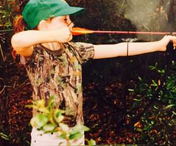 young child shooting a bow and arrow
